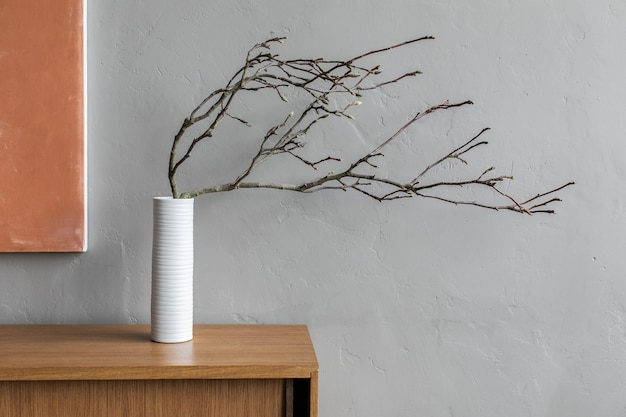 Композиция натюрморта с высушенной деревянной ветвью в белой керамической вазе. минималистичные украшения домашнего интерьера