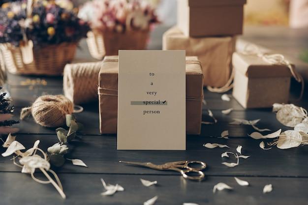 はさみと柔らかい花びらがテーブルの上に置かれたギフトボックスに寄りかかって特別な人のためのロマンチックなカードのある静物構成