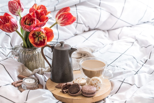 Still life cozy breakfast with coffee and flowers in the bedroom