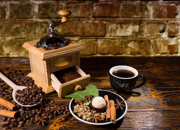 Still life of cup of hot brewed coffee on rustic wooden table beside hand grinder and small plate with truffle and variety of spice garnishes, surrounded by scattered roasted coffee beans
