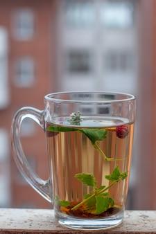 ハーブティーと静物カップ。背景にたくさんの窓がある赤い家。いちごの葉とベリーがカップに浮かんでいます。側面図。垂直フレーム。