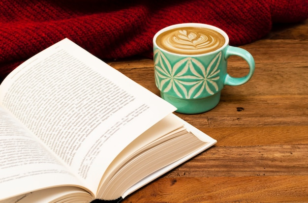 Still life details, cup of latte or cappuccino coffee with a book and red sweater on a wooden table.