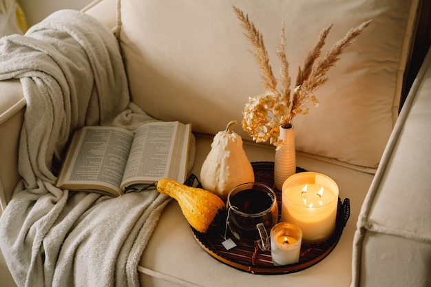 Still life details in home interior of living room. pumpkin and cup of tea with candles on a serving tray. rest and reading. cozy autumn