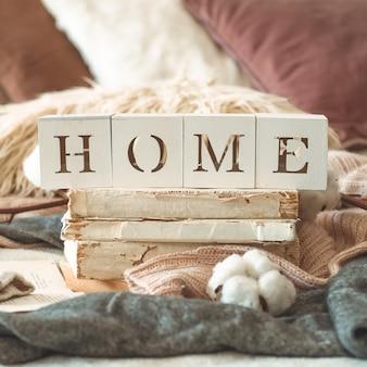 Детали натюрморта в домашнем интерьере гостиной и надпись home. книги и чашка чая с конусом и хлопком. читай, отдыхай. уютная осенняя или зимняя концепция, трикотаж. уютная осенне-зимняя концепция