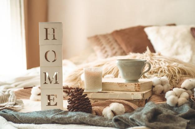 リビングルームのインテリアと碑文homeの静物詳細。本とコーンとコットンのお茶。読んで、休憩。居心地の良い秋または冬のコンセプト、ニット。居心地の良い秋冬コンセプト