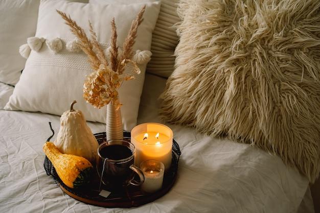居間の家の内部の静物の詳細。カボチャと一杯のお茶とキャンドルをサービングトレイに。居心地の良い秋