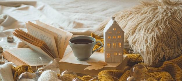 リビングルームのインテリアの静物詳細。セーターとキャンドルハウスと本の秋の装飾とお茶のカップ。読んで、休憩。居心地の良い秋や冬のコンセプトです。