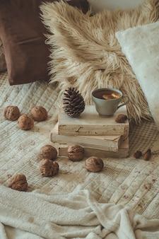 Детали натюрморта в домашнем интерьере гостиной. свитера и чашка чая с конусом, орехами и осенним декором на книгах. читай, отдыхай. уютная осенняя или зимняя концепция.