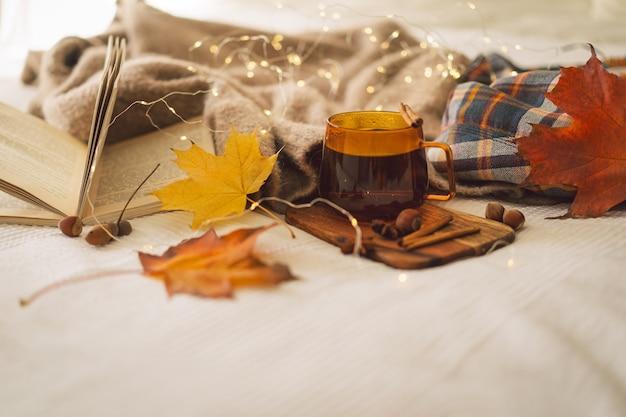 秋の装飾と本を備えた家のインテリアセーターとお茶の静物の詳細は残りを読む