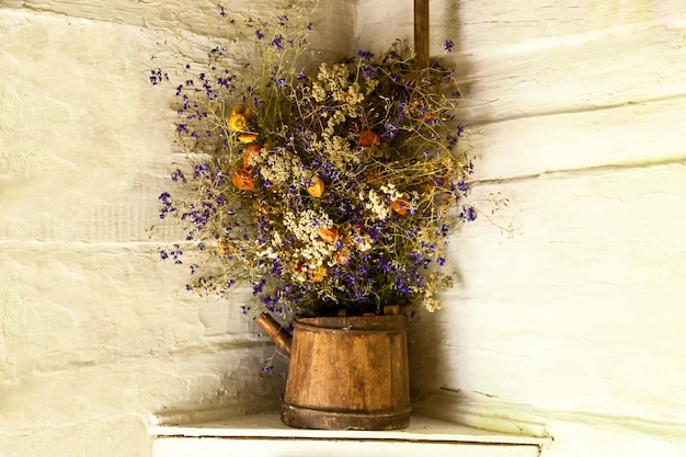 Still life of dried flowers on white wall background bouquet of wild flowers in niche of old stone