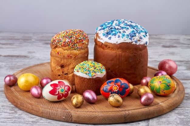 木の板の静物イースターケーキと卵。甘いアイシングトップと色付きの装飾的な卵と茶色のカップケーキ。