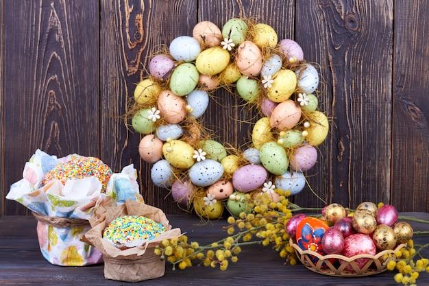 素朴な背景に静物イースターのシンボル。カラフルな卵と暗い木製の背景に柳の枝とイースターケーキ。