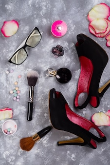 Still life of fashion woman. women's fashion with petals of roses, cosmetics, glasses and