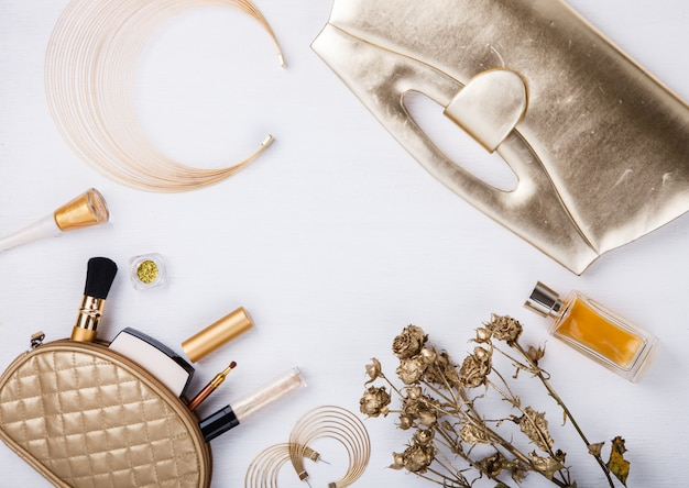 Still life of fashion woman. women's set of fashion accessories in golden color.