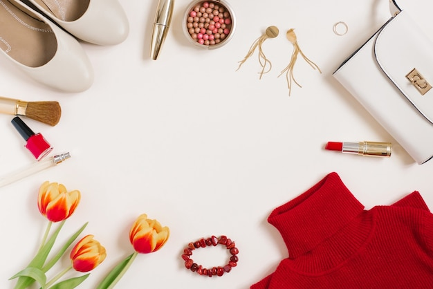 Still life of a fashionista. women's cosmetic background. flat lay for valentine's day. stylish accessories, a bouquet of tulips and blogger's clothes. copying a space