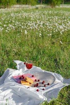 Still life and food photo cherry and waffle berries lie on wicker round napkin and crumpled fabric