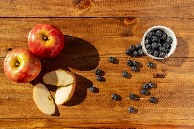 木製のテーブルに秋の果物、ナッツ、ベリーと感謝祭の静物。ヘルシーフード、