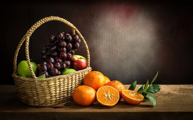 Still lifeビンテージの木製テーブルのバスケットに新鮮なオレンジ、アップル、ブドウミックスフルーツ