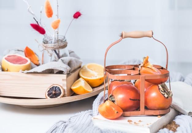 保持の朝食コンセプトのサービングテーブル準備のバスケットの静物新鮮な柿