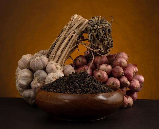 古い木製のテーブルに分離された静物ニンニク、エシャロット、黒コショウ。