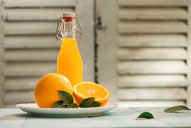 コピー スペースの背景を持つヴィンテージの木製テーブルに新鮮なオレンジ ジュースの静物ガラス