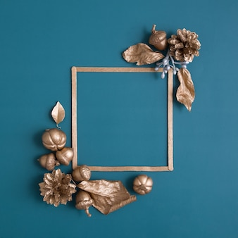 Still life of gold and white cones pumpkins acorns with a frame for text on a turquoise background m...