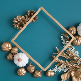 Still life of gold and white cones, pumpkins, acorns with a frame for text on a turquoise background. minimalistic autumn concept with copy space