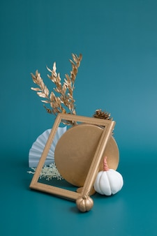Still life of gold and white elements on a turquoise background. minimalistic autumn concept