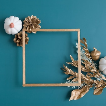 Still life of gold and white elements with a frame for text on a turquoise background. minimalistic autumn concept