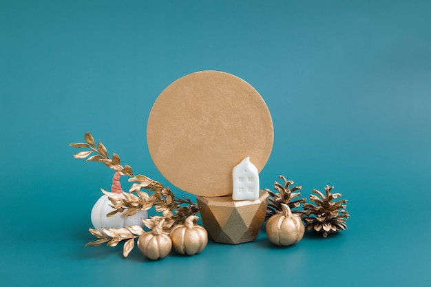 Still life of gold and white pumpkins, acorns and a house on a turquoise background. minimalistic autumn concept with copy space