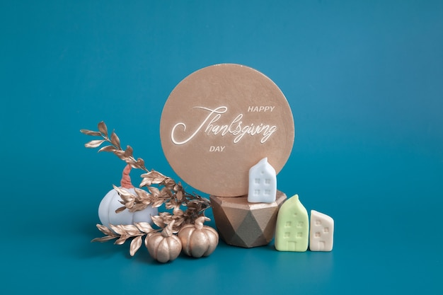 Still life of gold and white pumpkins acorns and miniature houses on a turquoise background minimali...