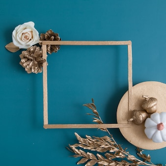 Still life of golden acorns cones podium with frame and pumpkin for text on a turquoise background