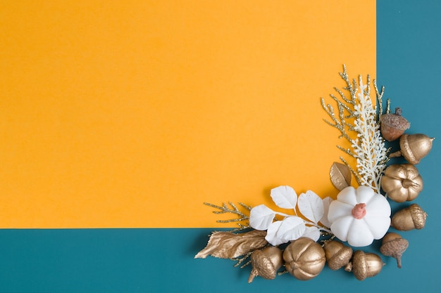 Still life of golden acorns leaves and pumpkins on an orangeturquoise background minimalistic autumn...