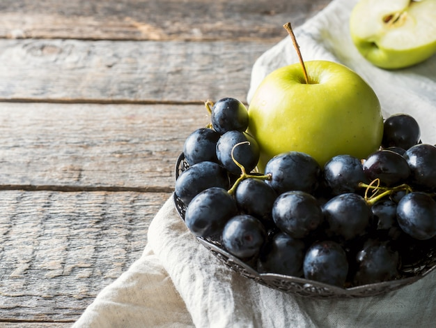 Still life grapes and apples in a vintage plate on rustic wooden background