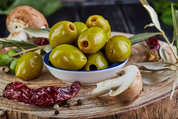 Still life of green fresh olives, red pepper and fresh mushrooms with olive tree leaves on a dark wooden close up