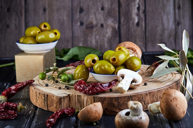 Still life of green fresh olives, red pepper and fresh mushrooms with olive tree leaves on a dark wooden