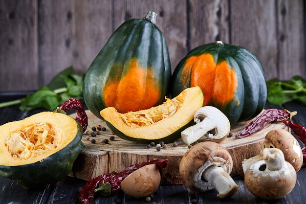 Still life of green-orange chestnut pumpkins and sliced pumpkin with red pepper and mushrooms lying on a dark wooden background