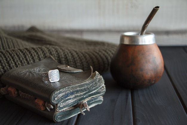 Still life of hand crafted artisanal yerba mate tea leather calabash gourd with straw, leather notebook, sweater and ring on a black painted table,
