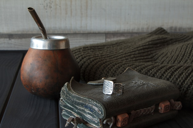 Still life of hand crafted artisanal yerba mate tea leather calabash gourd with straw
