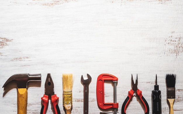 A still-life of handy tools on a rustic white wood background.
