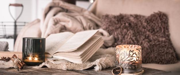 本とキャンドル、居心地の良いベッドカバーのテーブルの上のインテリアの静物家庭の雰囲気