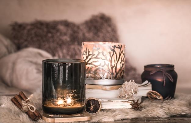 Натюрморт домашней атмосферы в интерьере со свечами и книжкой на столе из уютных покрывал