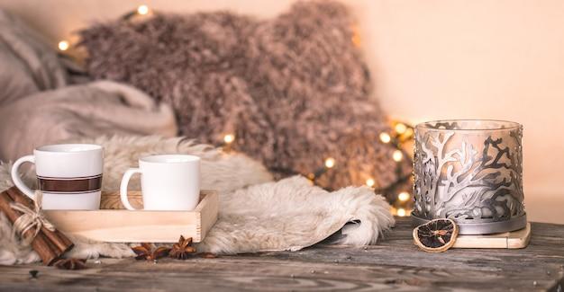 居心地の良いベッドカバーのテーブルにカップとキャンドルのあるインテリアの静物家庭の雰囲気