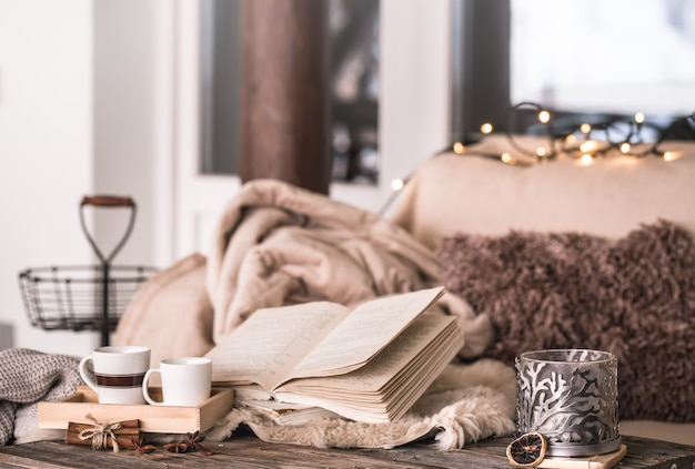 Still life home atmosphere in the interior with cups, a book and candles, on the background of cozy bedspreads