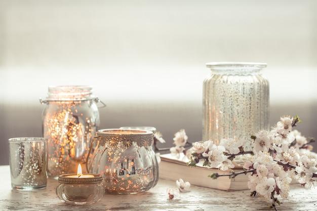 정물. 거실의 집 아늑한 아름다운 장식, 봄 꽃과 나무 배경에 촛불이 달린 꽃병, 인테리어 세부 개념