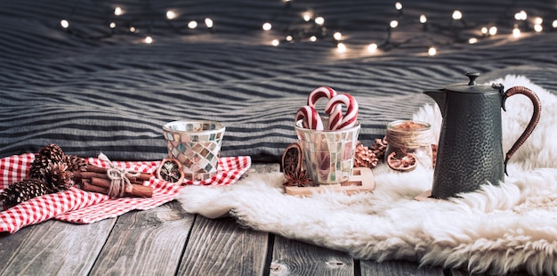 Still life home decorations with a teapot on a wooden background in the interior of the room with light in the background, a holiday concept