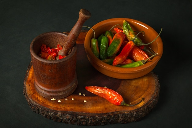 Still life of hot peppers in a mortar next to a bowl on a dark surface