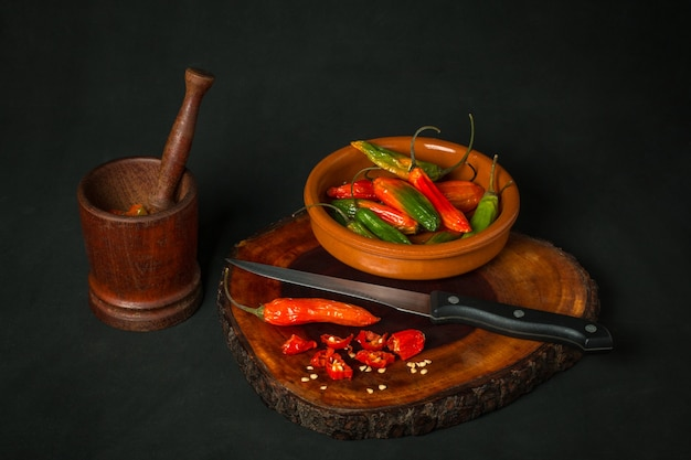 Still life of hot peppers in a mortar next to a bowl and a knife on a dark background