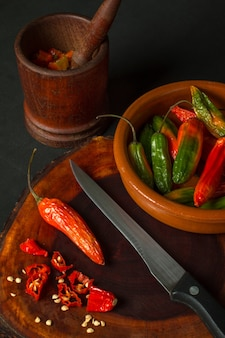 Still life of hot peppers in a mortar next to a bowl and a knife on a dark surface