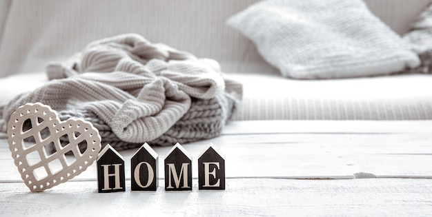 Still life in hygge style with wooden word home and knitted element